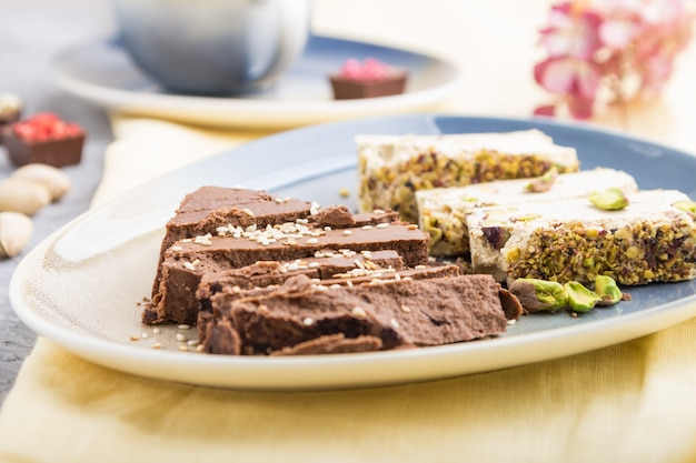 Traditional arabic sweets sesame halva with chocolate and pistachio and a cup of coffee on a gray concrete surface. side view, selective focus.