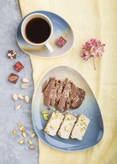 Traditional arabic sweets sesame halva with chocolate and pistachio and a cup of coffee on a gray concrete surface. top view, close up.