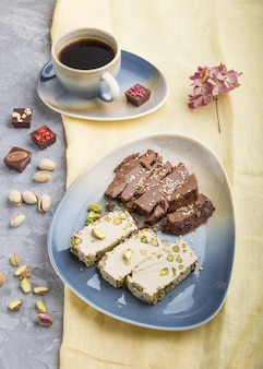 Traditional arabic sweets sesame halva with chocolate and pistachio and a cup of coffee. side view, close up.