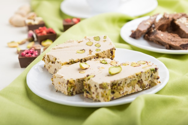 Traditional arabic sweets sesame halva with chocolate and pistachio and a cup of coffee. side view