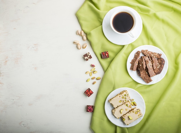 Traditional arabic sweets sesame halva with chocolate and pistachio and a cup of coffee. top view