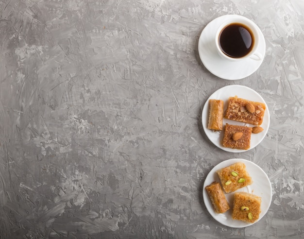 Traditional arabic sweets on white plate and a cup of coffee.  top view