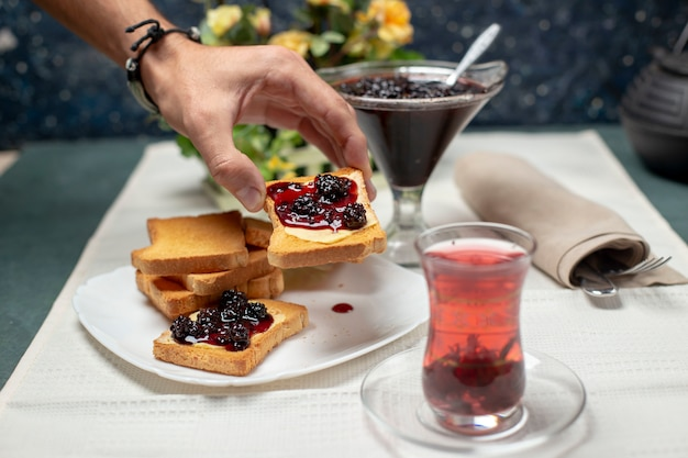 A traditional armudu glass of black tea with toasts with strawberry jam. a person taking a toast.