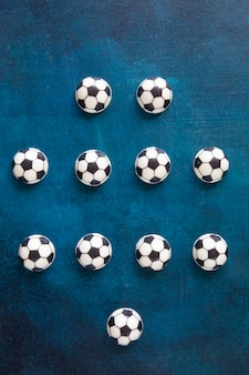 The traditional arrangement of players on the football field is four-four-two. players are marked with chocolate cakes in the form of balls for european football in black and white