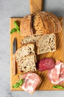씨앗과 돼지 고기 소시지와 살라미 전통 장인 빵 나무 커팅 보드에 재직했습니다. 돼지 고기 소시지와 샌드위치를 엽니 다.