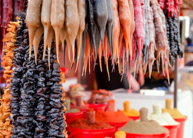 Traditional asian dessert churchkhela and different spices at street market,