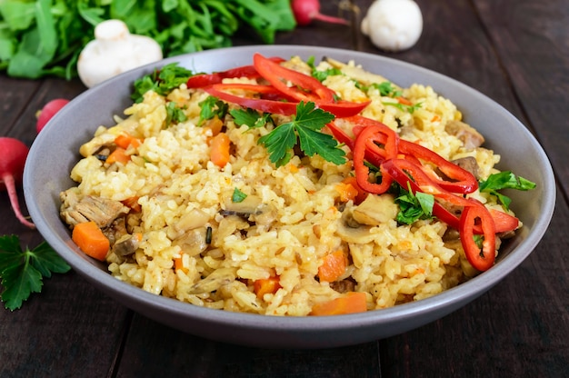 A traditional asian dish - pilaf with meat, mushrooms and pepper capi in a bowl on a dark wooden table.
