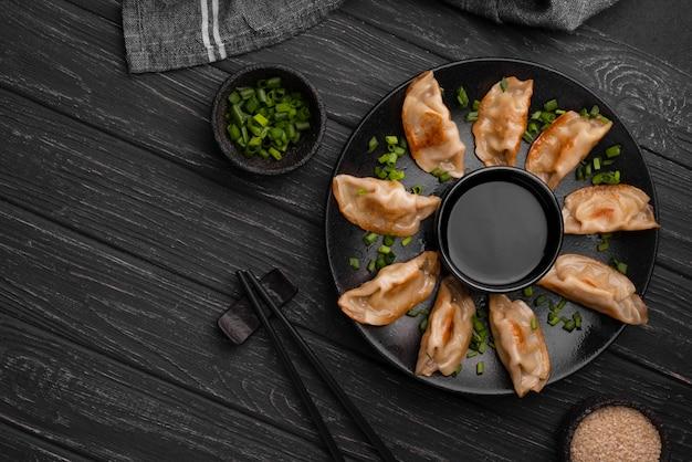 Традиционные азиатские пельмени на тарелке с палочками для еды и зеленью