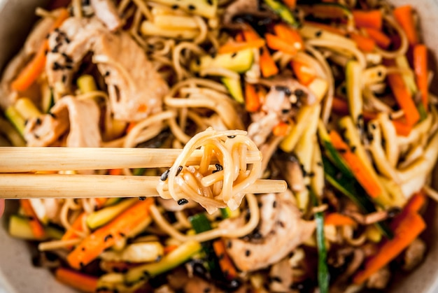 Traditional asian food. lunch stirfry: rice noodles, zucchini, carrots, bamboo, mushrooms