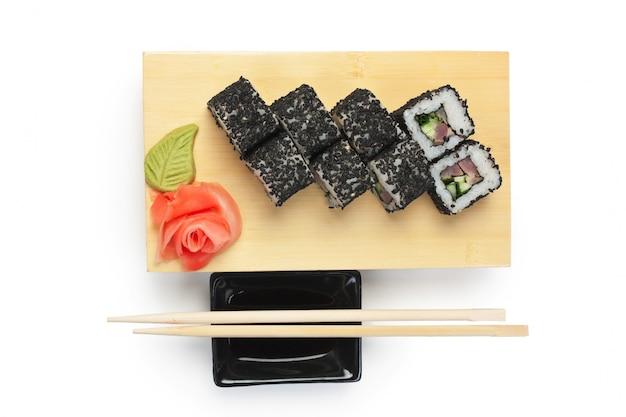 白い背景で隔離の木製プレートに伝統的なアジア料理の寿司
