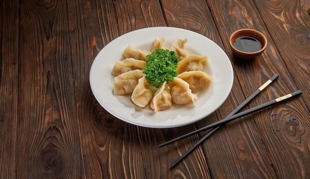 Традиционные азиатские жареные пельмени гёдза на белой тарелке и соевый соус с парой палочек для еды на темном деревянном столе, вид и пространство для копирования