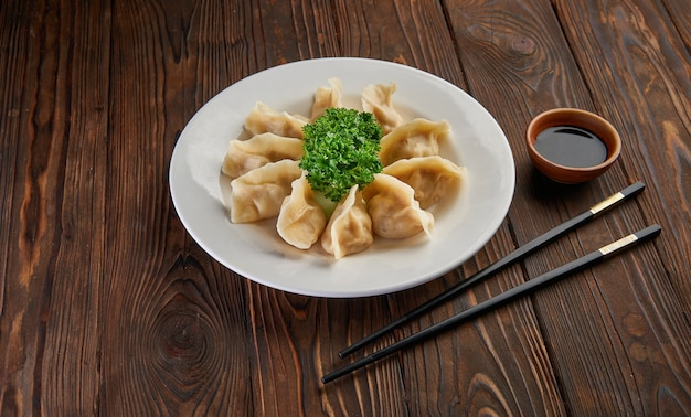 Traditional asian fried dumplings gyoza on white plate and soy sauce with pair of chopsticks on dark wooden table top view and copy space