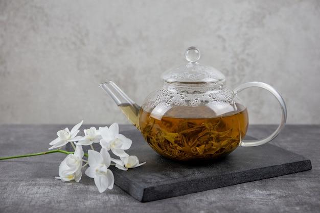 Традиционный азиатский зеленый чай в стеклянном чайнике на темном фоне