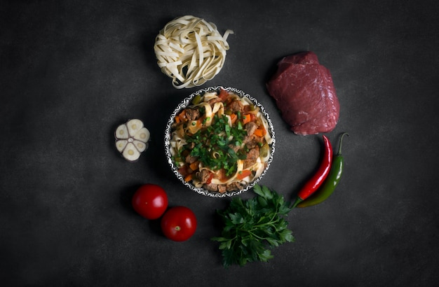 Traditional asian noodle lagman with vegetables and meat
