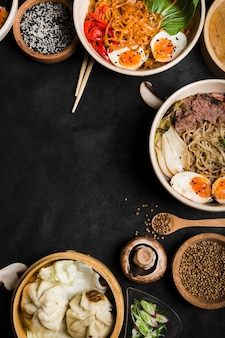 Traditional asian noodles bowls with steamed dumplings on black backdrop