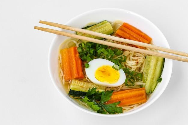 麺、ニンジン、ズッキーニ、ゆで卵、白い背景の上の伝統的なアジアのスープ、料理には通常ブイヨンと野菜が含まれています