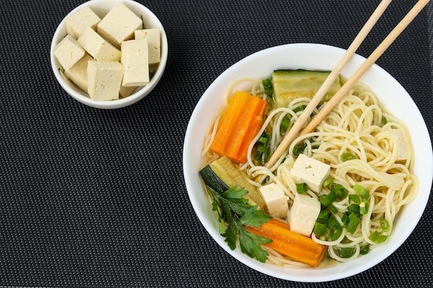 暗い背景に豆腐チーズ、麺、にんじん、ズッキーニを添えた伝統的なアジアのスープ。この料理には通常、ブイヨンと野菜、上面図、コピースペースが含まれています