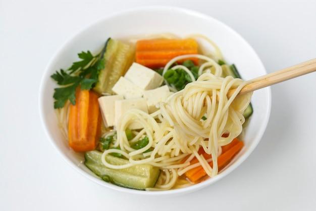 白い背景に豆腐チーズ、麺、にんじん、ズッキーニを使った伝統的なアジアのスープ、料理には通常ブイヨンと野菜が含まれています、水平方向、クローズアップ