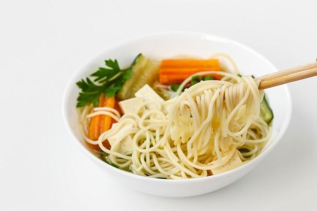 Традиционный азиатский суп с сыром тофу, лапшой, морковью и цукини на белом фоне