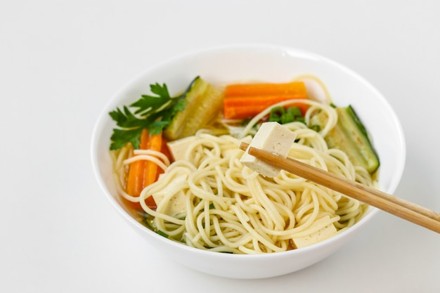 Traditional asian soup with tofu cheese, noodles, carrots and zucchini. this dish usually contains bouillon and vegetables