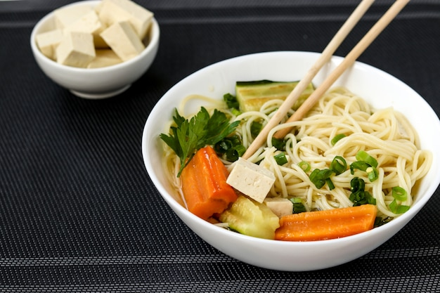 Traditional asian soup with tofu cheese, noodles, carrots and zucchini