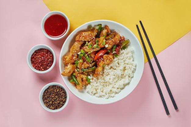 Традиционная азиатская уличная еда - курица в кисло-сладком соусе с порцией риса в белой миске на яркой, цветной поверхности. вид сверху