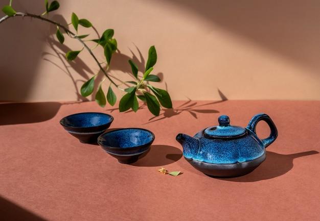 전통적인 아시아 다도 개념. 갈색 표면에 파란색 주전자와 차 컵입니다.