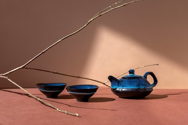 Traditional asian tea ceremony concept. blue teapot and tea cups on brown background.