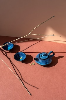 Traditional asian tea ceremony concept. blue teapot and tea cups on brown surface.
