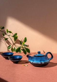 Traditional asian tea ceremony concept. blue teapot and tea cups on brown wall.