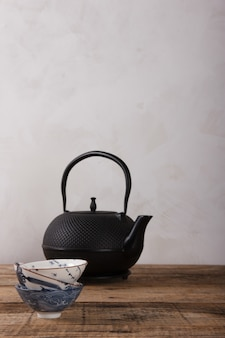 Traditional asian tea set - black iron teapot and ceramic teacups for tea ceremony on a wooden table. vintage style.