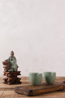 Traditional asian tea set - ceramic teacups for tea ceremony on a wooden table. vintage style.
