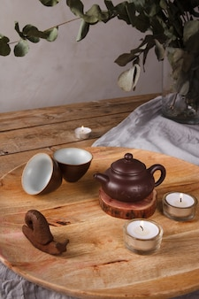 Traditional asian tea set - ceramic teapot and teacups for tea ceremony on a wooden table. vintage style.