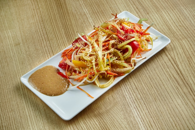 Traditional asian vegetable salad with peanut sauce on a white plate on a wooden surface
