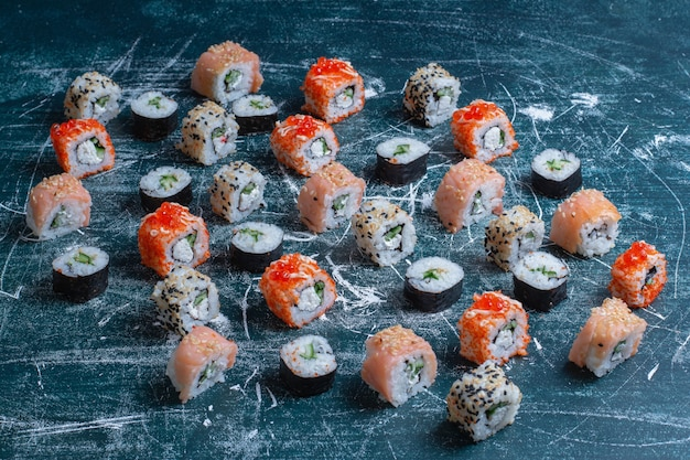 Traditional assorted sushi rolls on blue.