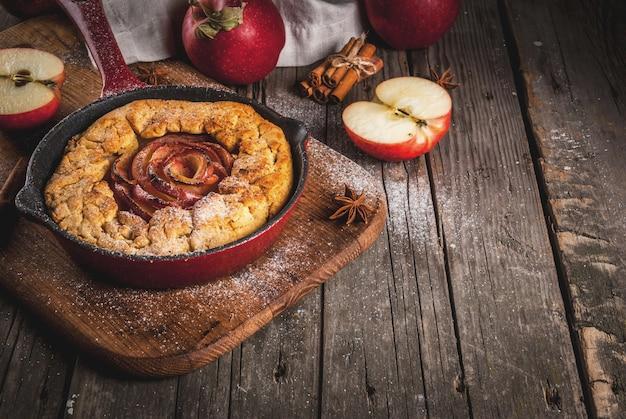 전통 가을 제빵, 추수 감사절 요리법, 유기농 사과와 계피를 곁들인 수제 통 곡물 애플 갤렛 파이, 철 주물 팬, 오래된 나무 테이블, 복사 공간