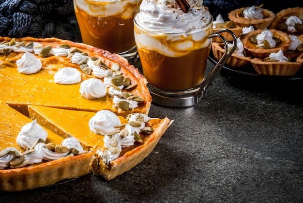 Traditional autumn dishes. halloween, thanksgiving. pumpkin pie, pumpkin tartlets with whipped cream & pumpkin seeds, pumpkin latte with cinnamon on black stone table with blanket. copy space