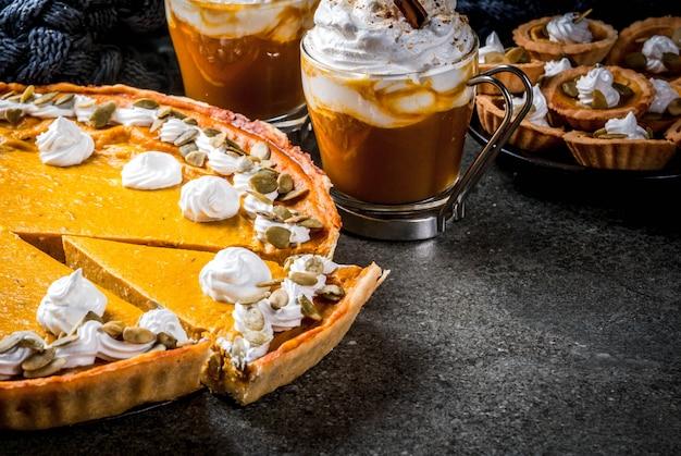 Традиционные осенние блюда. хэллоуин, день благодарения. тыквенный пирог, тыквенные тарталетки со взбитыми сливками и тыквенными семечками, тыквенный латте с корицей на черном каменном столе с одеялом. копировать пространство