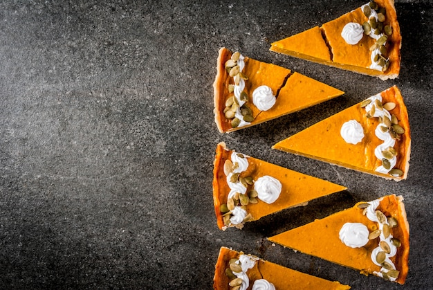 Traditional autumn dishes. halloween, thanksgiving. set of cuted pieces of spicy pumpkin pie with whipped cream & pumpkin seeds on black stone table.  copyspace top view