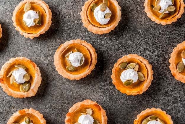 Traditional autumn dishes. halloween, thanksgiving. set of portioned mini spicy pumpkin tartlets with whipped cream & pumpkin seeds on black stone table. top view