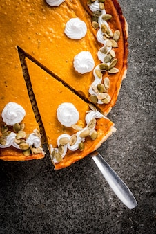 Traditional autumn dishes. halloween, thanksgiving. sliced spicy pumpkin pie with whipped cream & pumpkin seeds on black stone table. top view