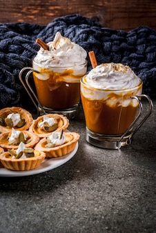 Traditional autumn dishes. halloween, thanksgiving. spicy pumpkin tartlets with whipped cream & pumpkin seeds, pumpkin latte with cinnamon on black stone table with blanket.  copyspace