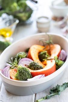 Традиционные осенние тыквенные блюда. запеченная на гриле тыква со специями, оливковым маслом, зеленью, брокколи и луком. на противне, на деревенском деревянном белом фоне.