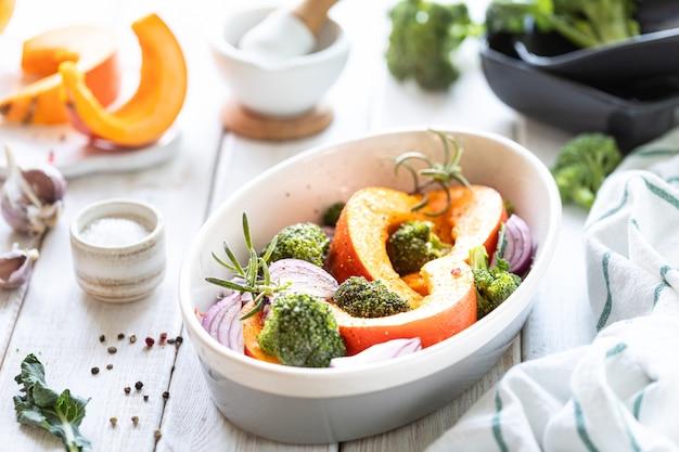 Традиционные осенние тыквенные блюда. запеченная на гриле тыква со специями, оливковым маслом, зеленью, брокколи и луком. на противне