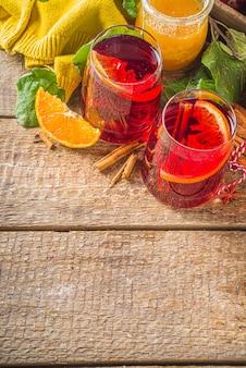伝統的な秋冬のアルコール飲料。柑橘類、リンゴ、スパイス、木製の素朴な背景を持つ熱い秋のフルーティーなサングリア
