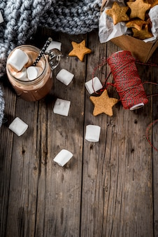 Traditional autumn winter drinks and treats. cup of hot chocolate with marshmallow and ginger biscuit stars, in gift box, old rustic wooden table. cozy atmosphere, copyspace