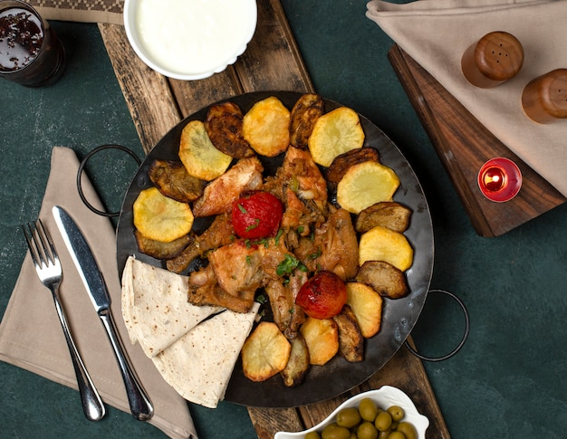Traditional azerbaijan dish served with yogurt on a wooden board with cutlery