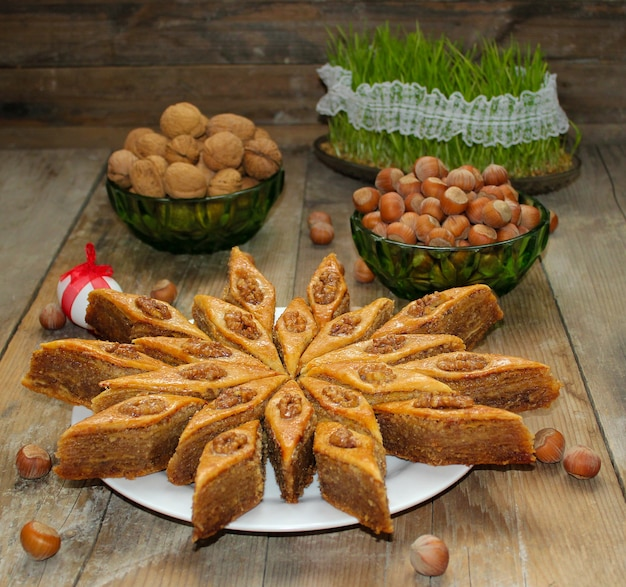 Traditional azerbaijan holiday cookies baklava on white plate on the rustic with nuts