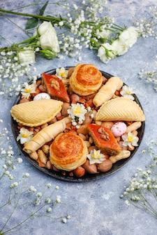 Традиционный азербайджанский праздник новруз печенья пахлавы и шакарбурас на черной подносной тарелке на сером бетоне