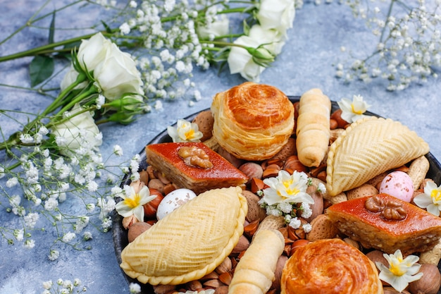 Traditional azerbaijan holiday novruz cookies baklavas and shakarburas on black tray plate on the grey concrete background